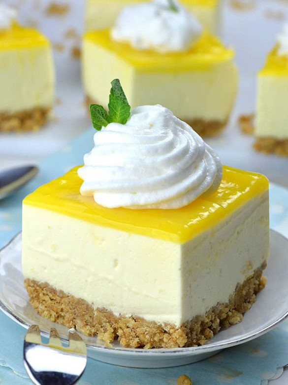 Piece of No Bake Lemon Cheesecake Bar on a white plate with cool whip topping in front of couple of pieces.