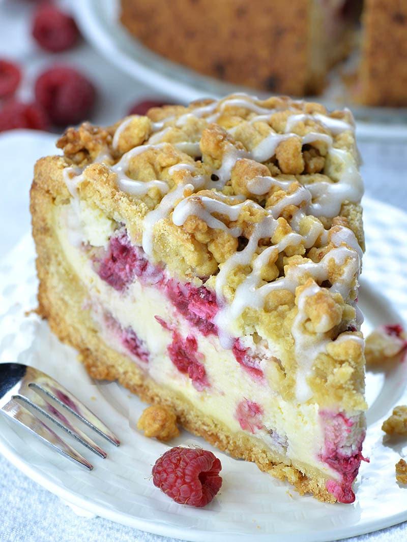 Big piece of Raspberry Cheesecake Crumb Cake on white plate with couple of raspberries beside.
