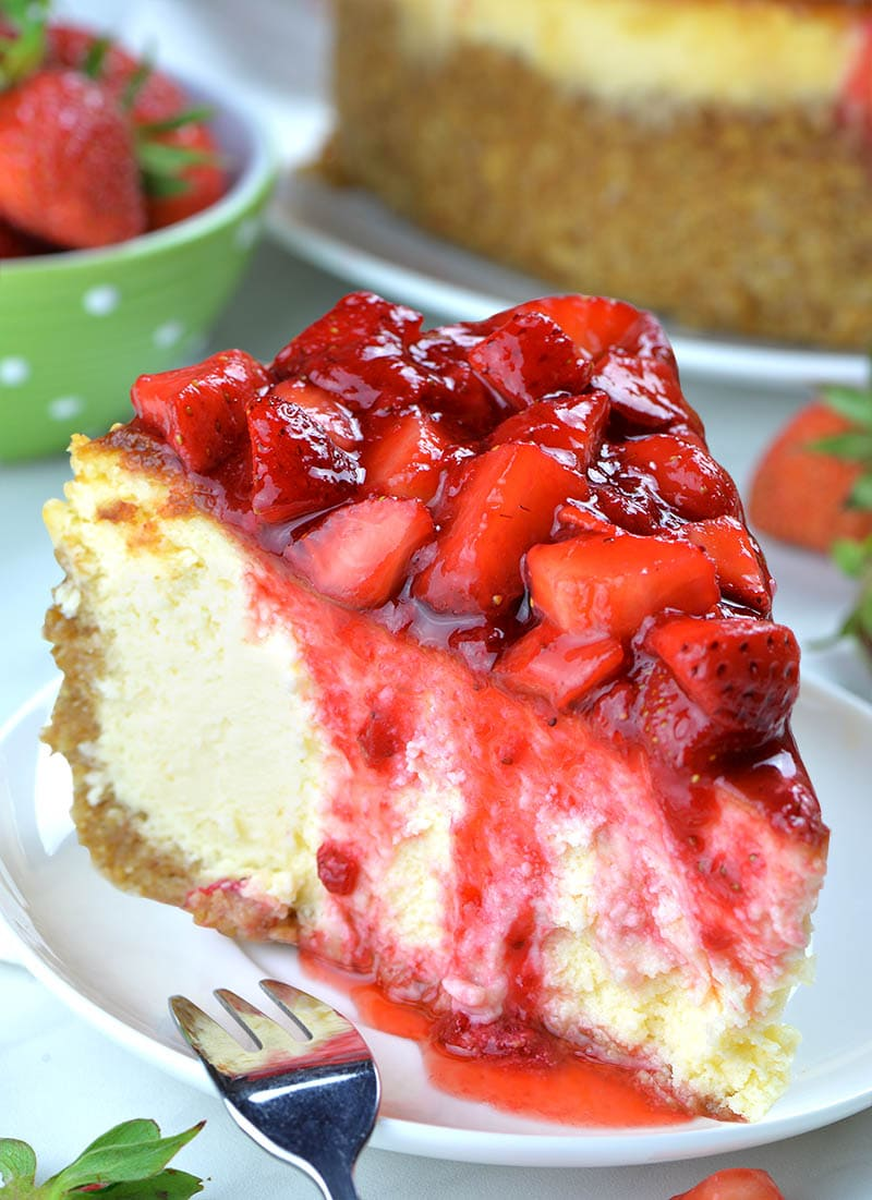 Big slice of Strawberry Cheesecake on a white plate and fork. Behind is green bowl full of strawberry .