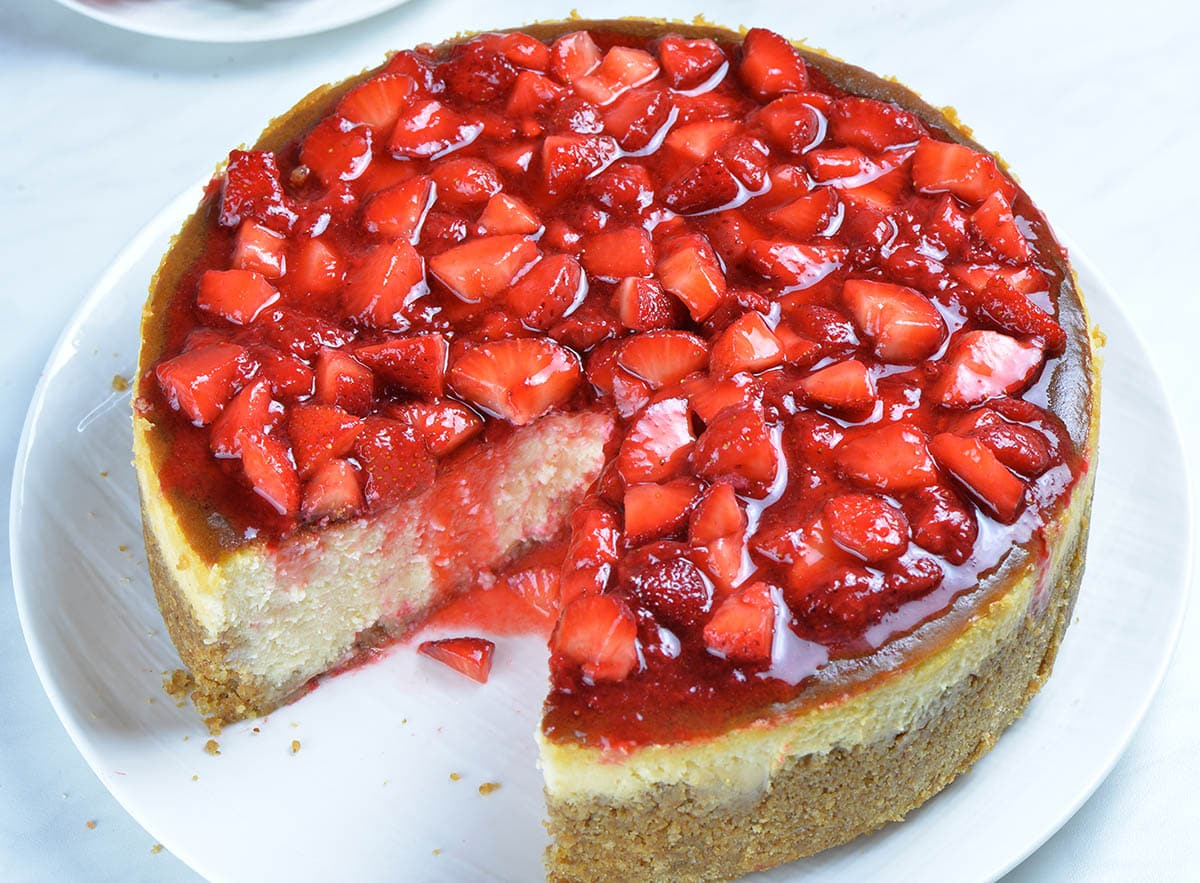 A whole Strawberry Cheesecake on a white plate photographed from above.