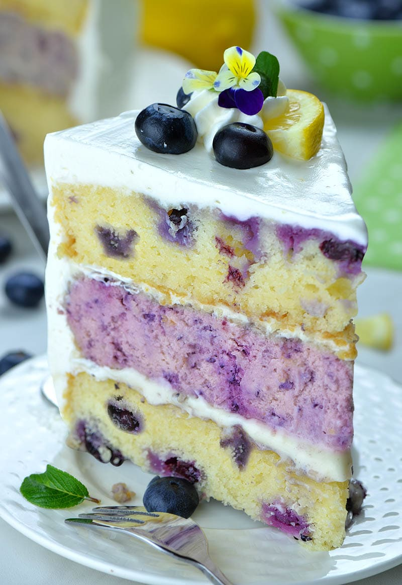 Piece of Lemon Blueberry Cheesecake Cake with there layers on a plate .