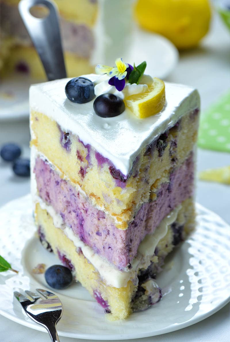 Piece of Lemon Blueberry Cheesecake Cake with there layers on a plate in front position.
