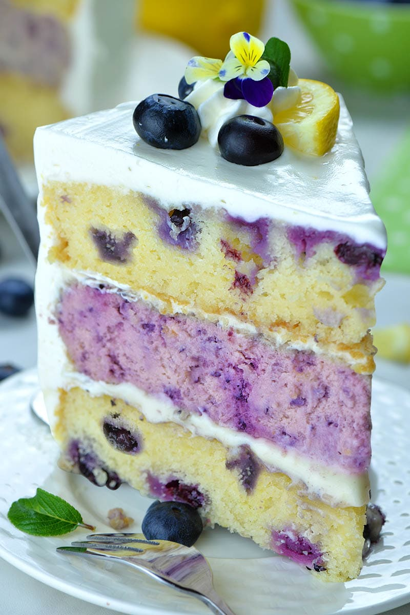 Lemon Blueberry Cake frosted with a tangy sweet lemon cream cheese frosting taste delicious on its own, but addition of Blueberry cheesecake layer in the middle makes truly showstopper dessert! #lemonblueberrycake #cakerecipe #blueberry #lemon