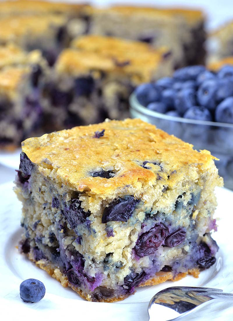 Piece of Blueberry Breakfast Cake on a white plate with a bunch of cakes and blueberries behind.
