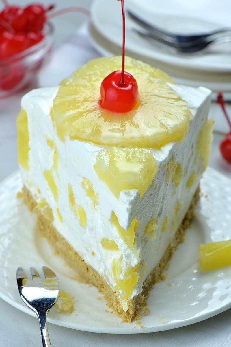 Slice of no bake pineapple cake with pineapple and maraschino cherry on top.