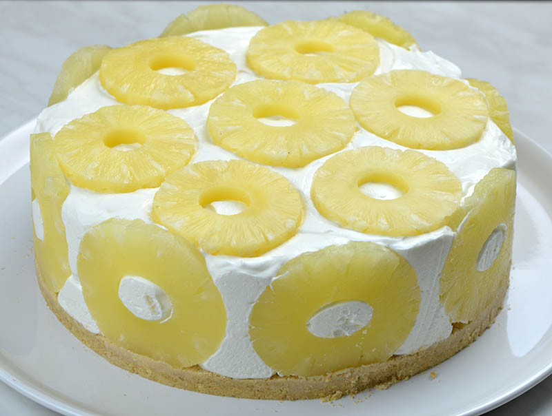 No bake pineapple cake on a serving plate garnished with pineapple slices.