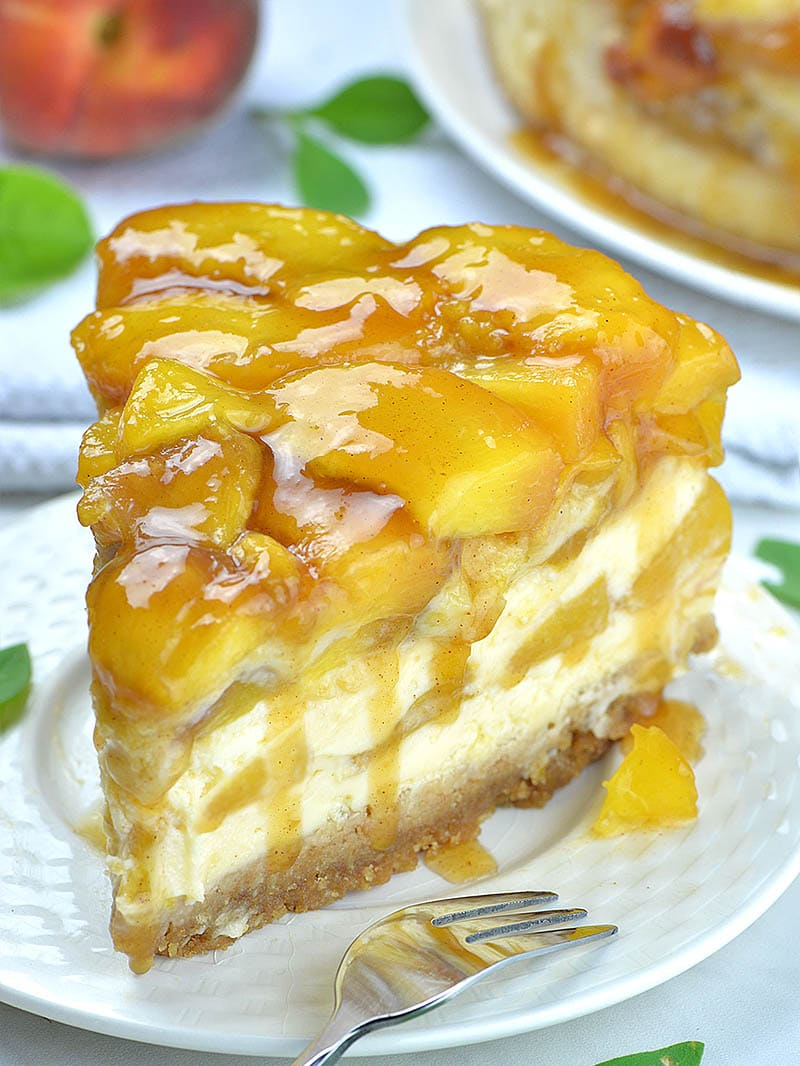 Slice of peach cobbler cheesecake on a plate.