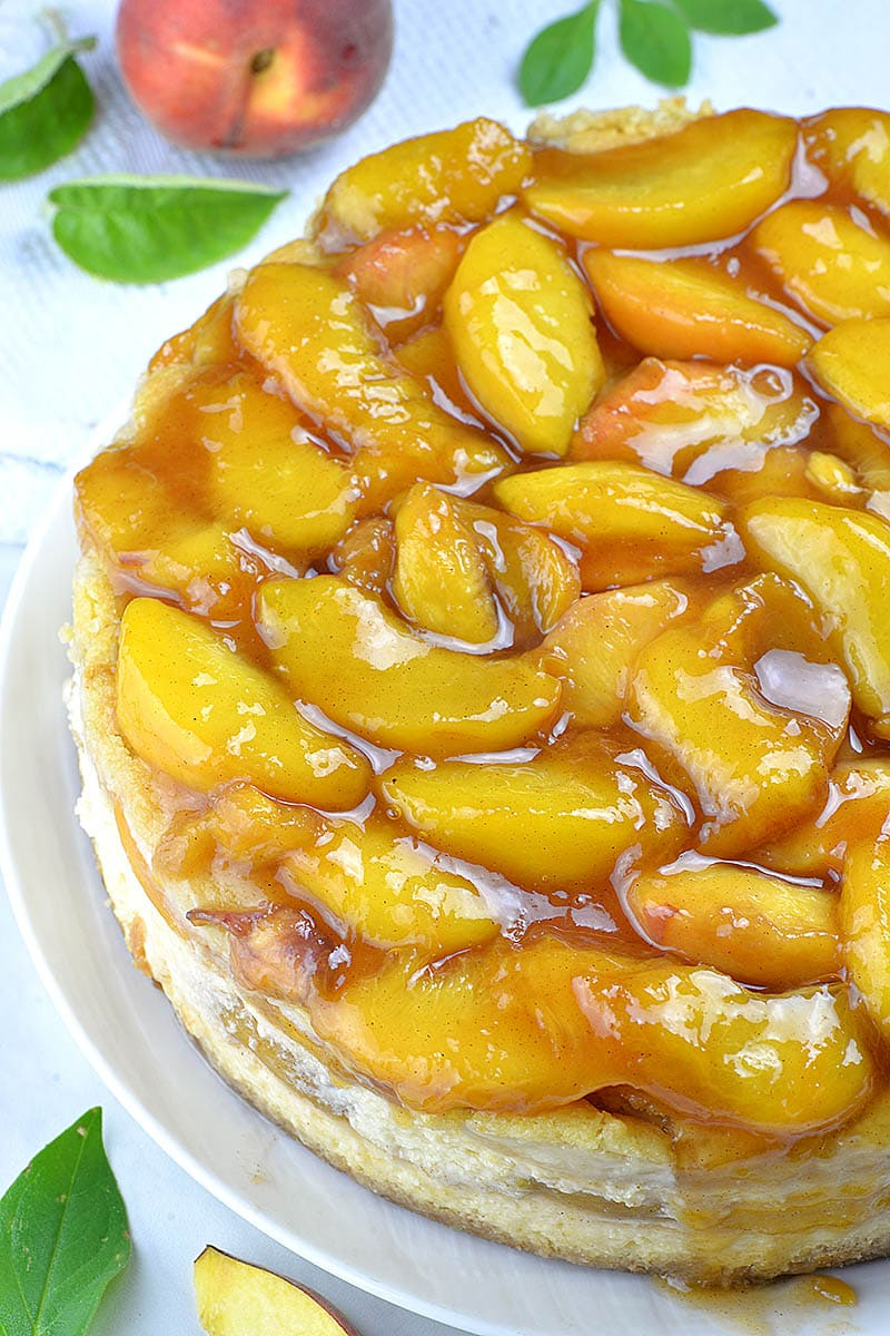 Peach cobbler cheesecake with sliced peaches and caramel sauce on top.