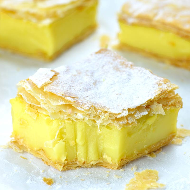 Vegan lemon custard slice with puff pastry crust dusted with powdered sugar.