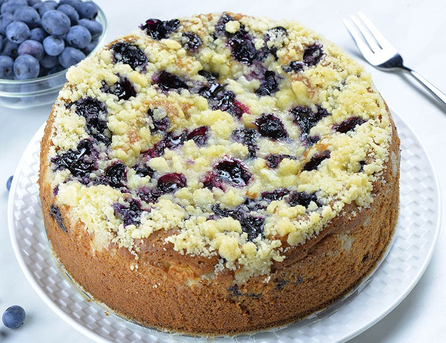 Whole blueberry coffee cake with streusel crumbs on top and a bowl of fresh blueberries behind the cake..