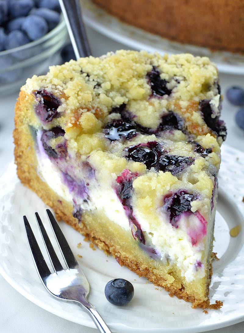 Piece of blueberry coffee cake served with a fork and fresh blueberry on white plate.