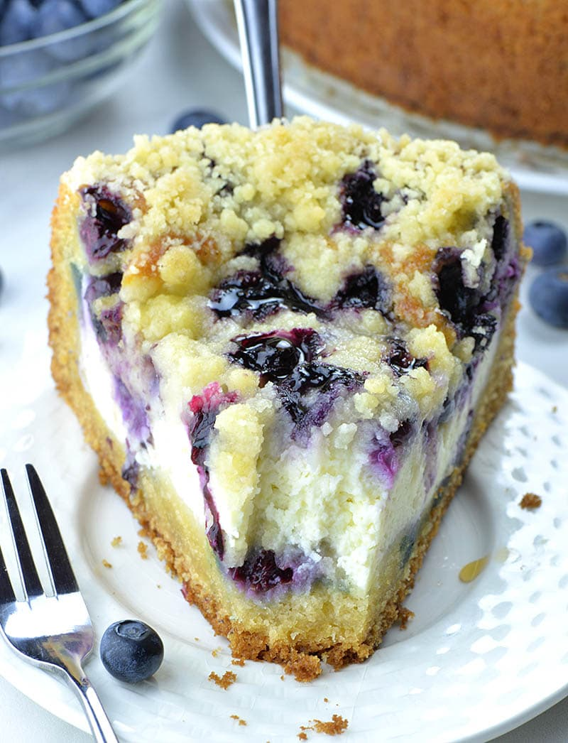 Piece of blueberry cream cheese coffee cake on a plate with fresh blueberry and crumbs on the white plate.