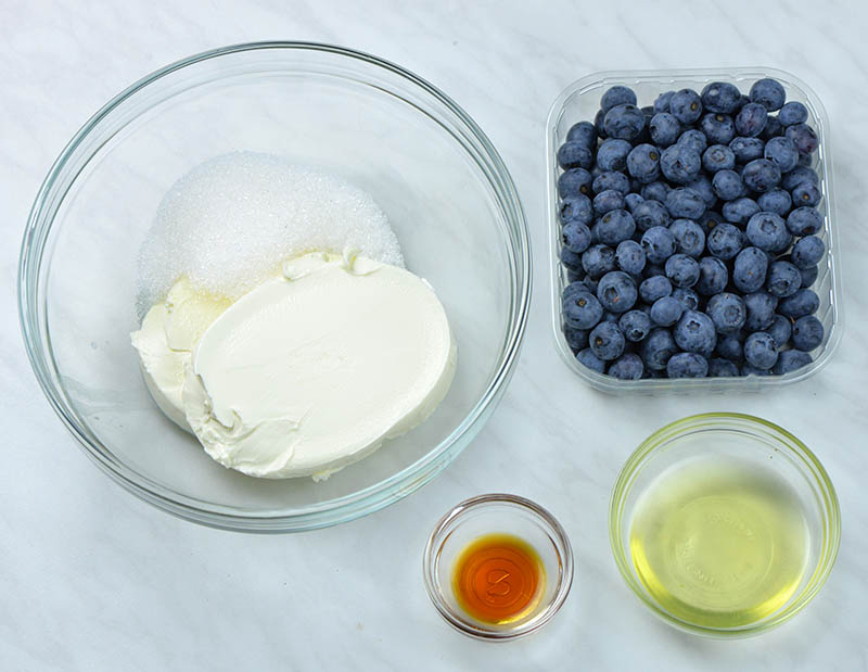 Ingredients for cream cheese filling prepared in glass bowls: cream cheese, vanilla extract, egg white and fresh blueberries.