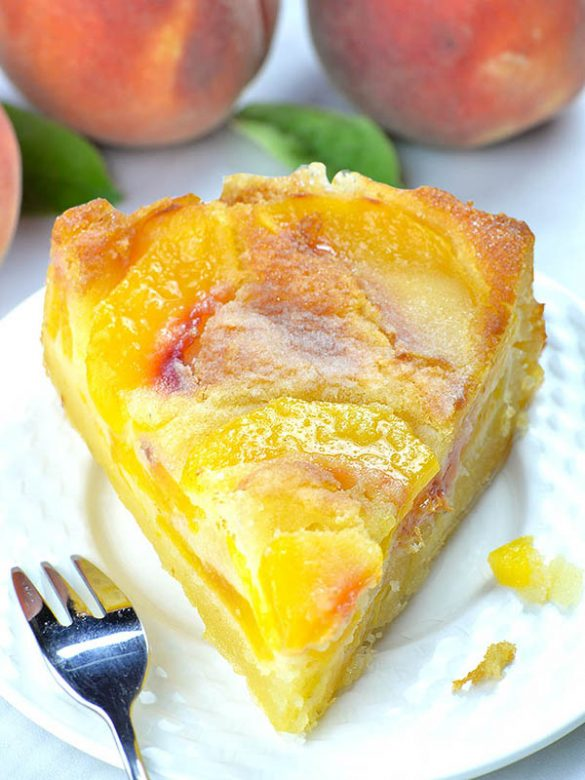 Piece of peach cake on white plate - bottom part is packed with peaches and has a dense, custard texture, while the top layer has cake-like texture.