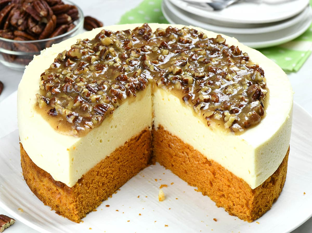 Pumpkin bread cheesecake with pecan praline topping on a white plate.