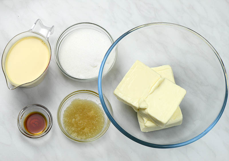 Bowls with ingredients for cheesecake layer: cream cheese, sugar, condensed milk, vanilla and gelatin.