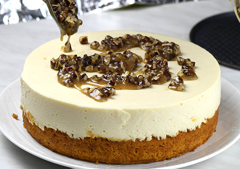 Adding pecan praline topping with a spoon on top of pumpkin bread cheesecake.