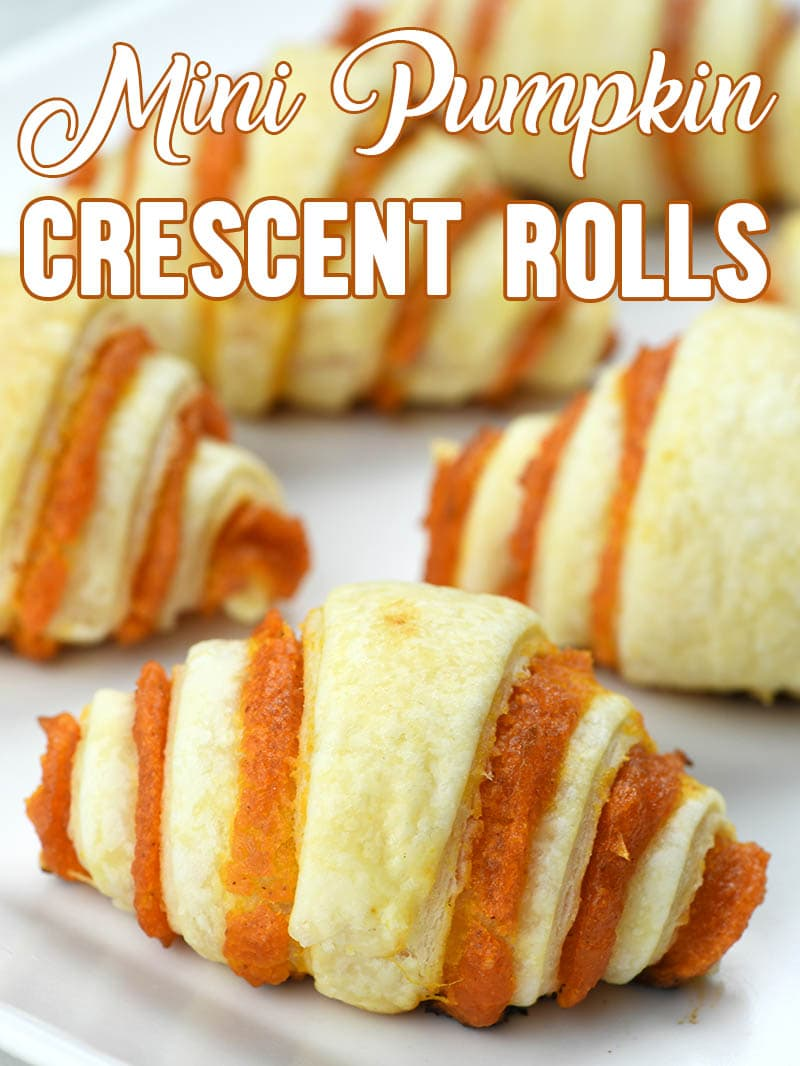 Bunch of Mini Pumpkin Crescent Rolls on parchment paper.