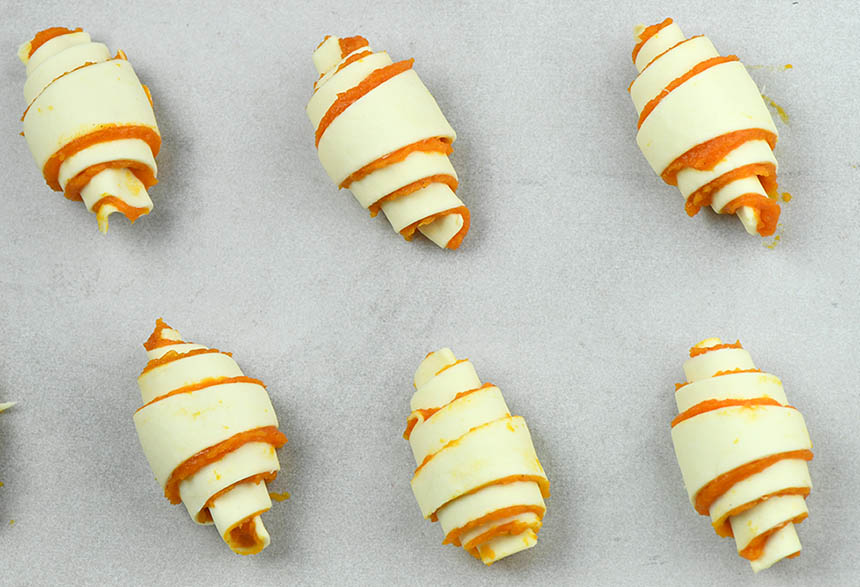 Mini Pumpkin pie crescent rolls on a baking sheet lined with parchment paper.