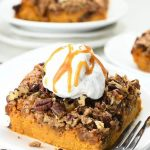 Pecan pumpkin crunch cake with whipped cream and caramel on top
