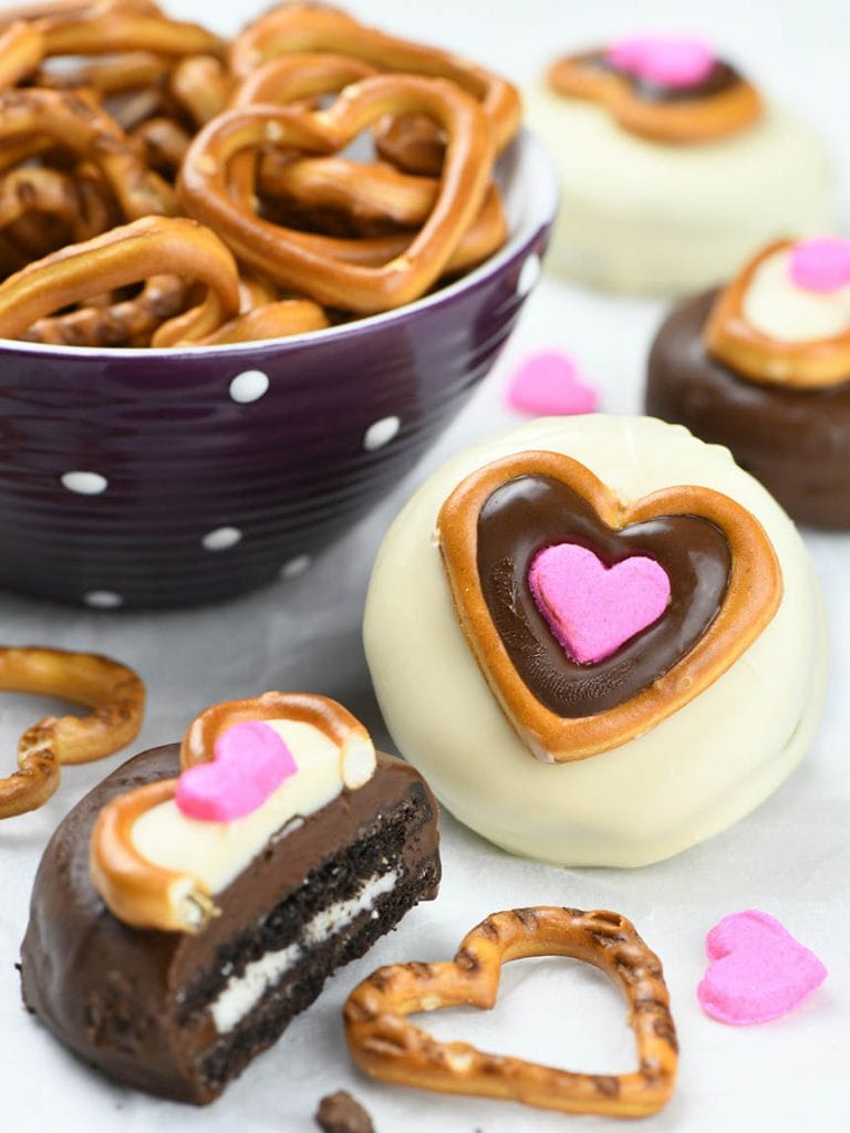 Oreo cookies dipped in white and dark chocolate, decorated with pretzel and candy hearts look and taste amazing.