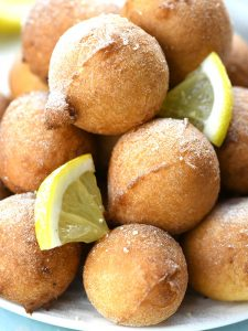 Bunch of crispy and golden Lemon Fritters on a plate.