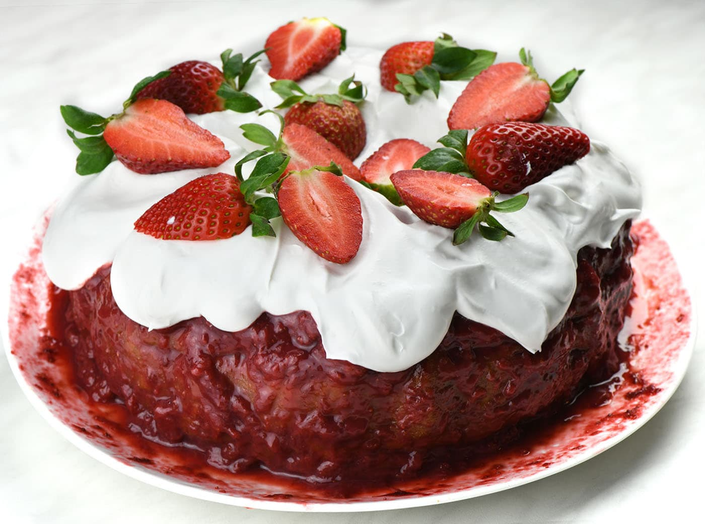 Whole Strawberry Bundt Cake on a white plate.