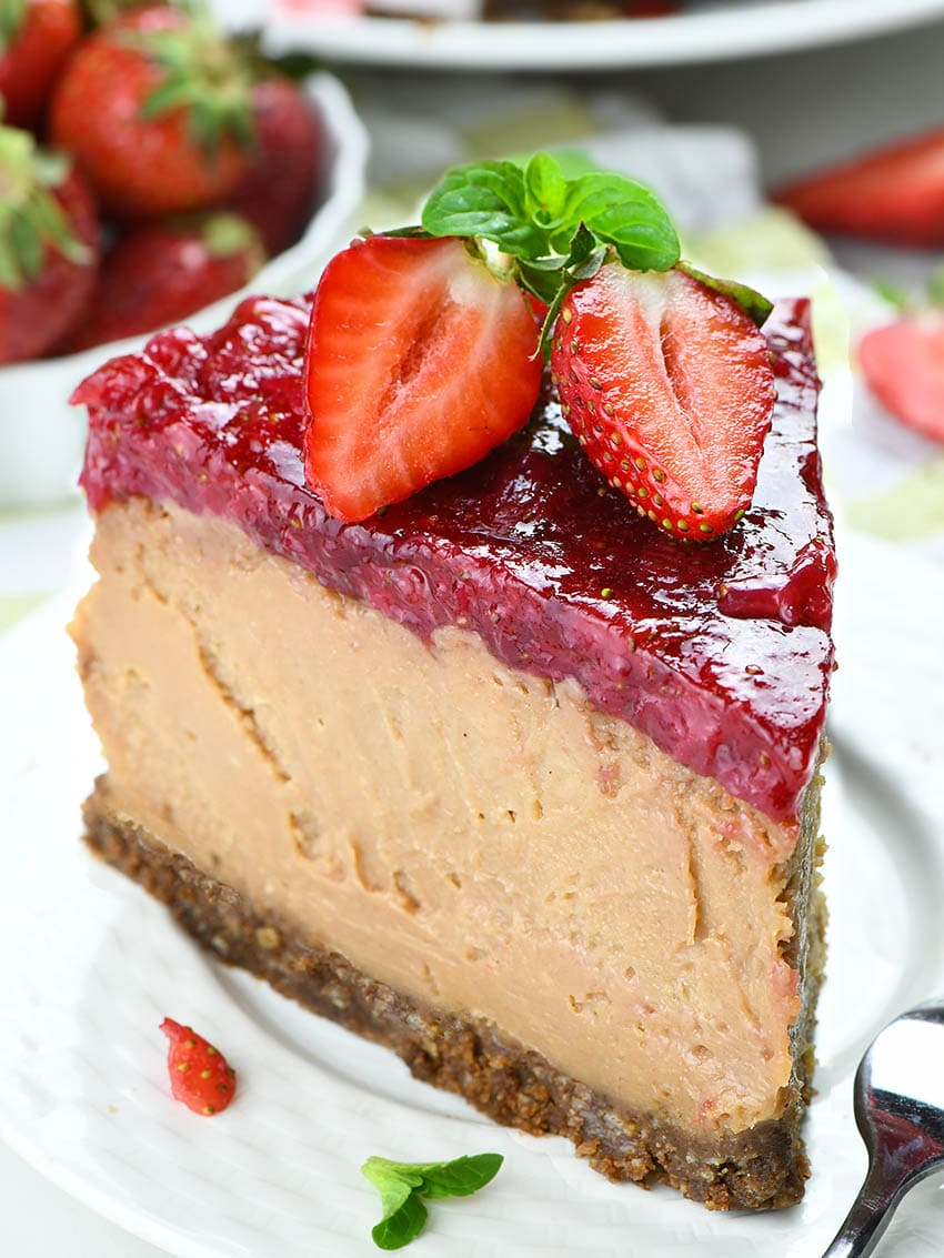 Piece of Strawberry Chocolate Cheesecake on a white pate garnished  with two half strawberries.