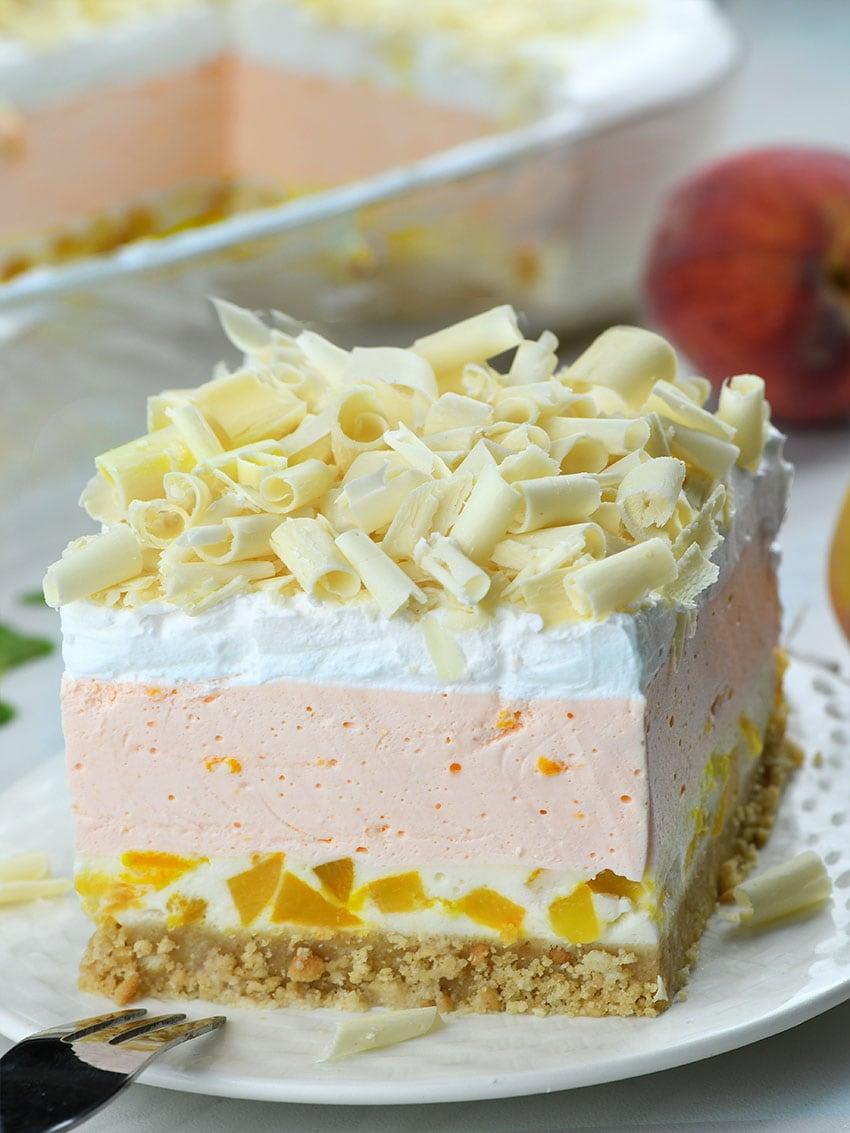 No Bake Peach Jello Lasagna on a white plate with peaches behind.