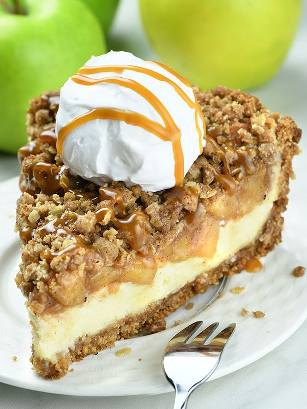 Apple Crisp Cheesecake on white plate with whipped cream ball on top and caramel topping.