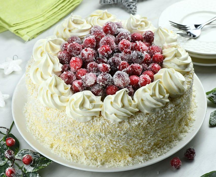 Whole White Chocolate Cranberry Layered Cake with Christmas decoration around.