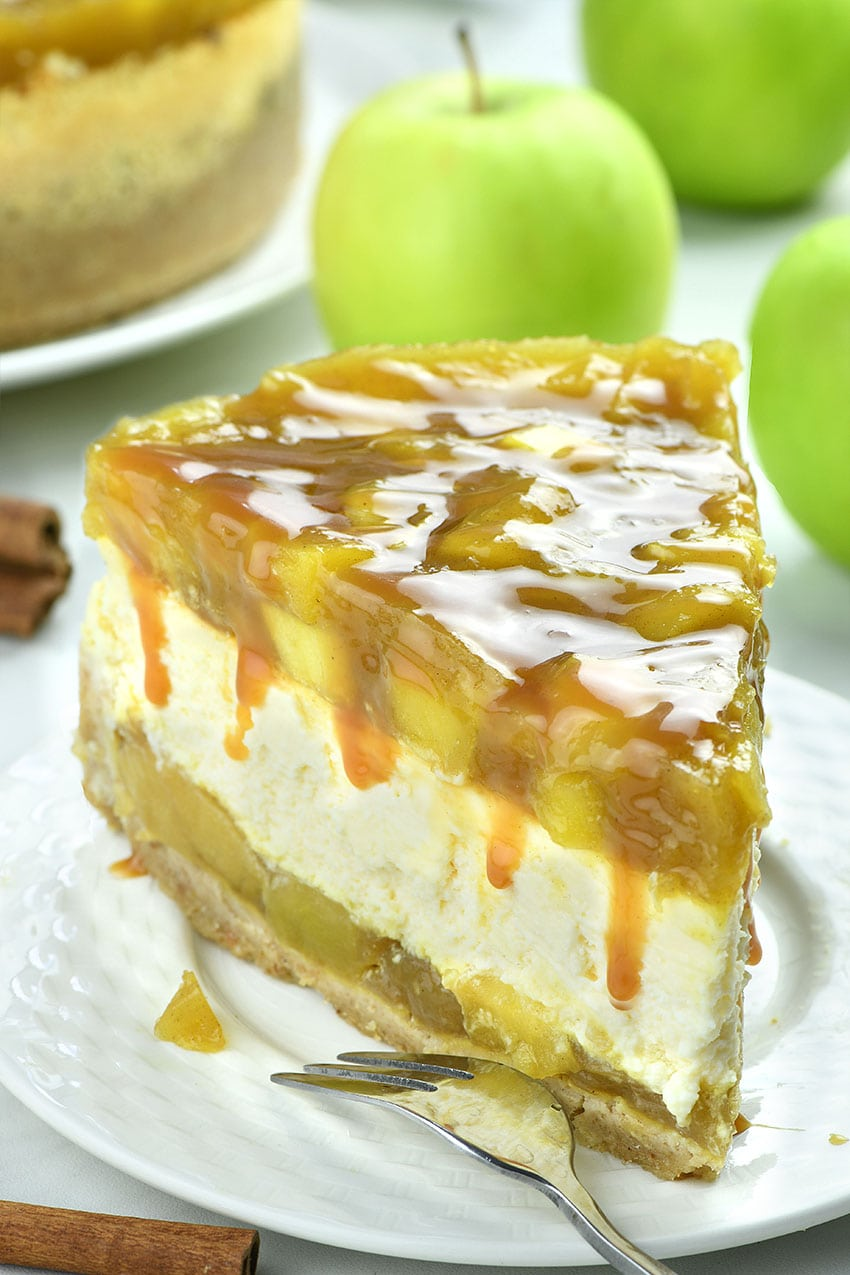 Piece of Apple pie Cheesecake on a white plate with bunch of apples behind.