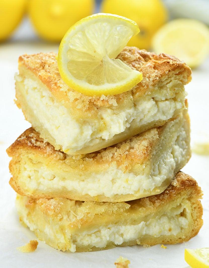 Couple of Lemon Cream Cheese Bars garnished with sliced lemons with couple of whole lemons behind.