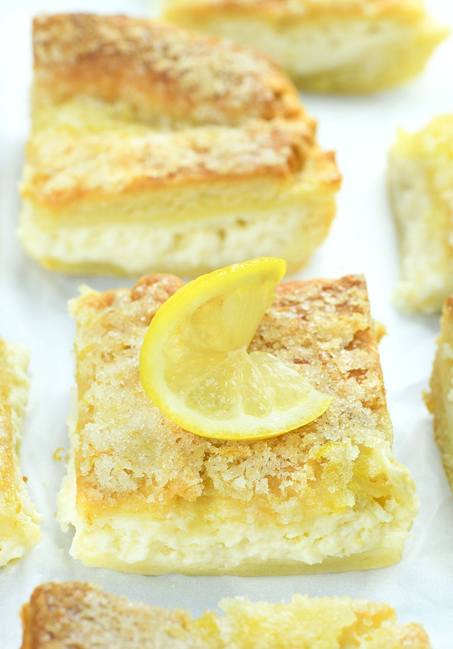 Big slice of Lemon Cream Cheese Bars garnished with lemon slice.